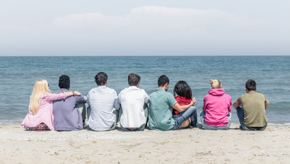 group of friends sitting on the beach