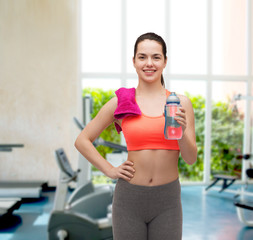 sporty woman with towel and water bottle