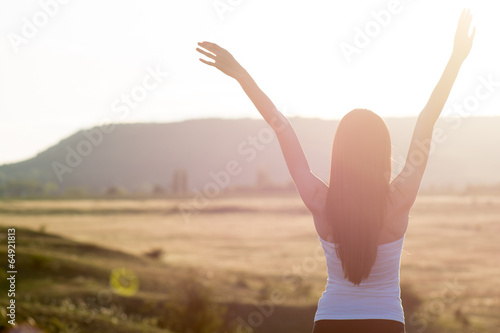 Tuinposter Ontspanning cheering woman open arms to sunrise