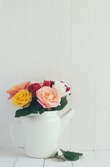 colorful roses in white enamel coffee pot