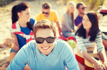 smiling man in sunglasses on the beach