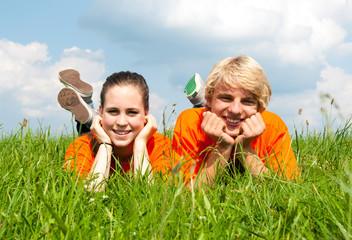 Teenager liegen im Gras
