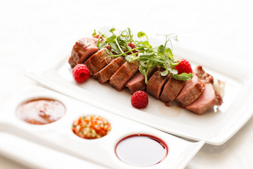 grilled duck breast covered with sweet red fruit sauce