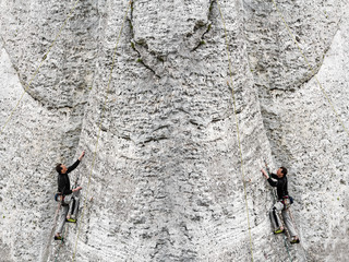 Concept of the same man climbing rocky mountain from both direct