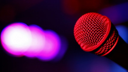 Microphone on stage with a colourful lights in background