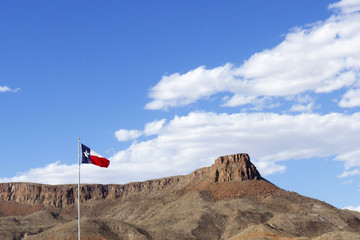 Texas State Flag with Blue Sky and Rock Mesa
