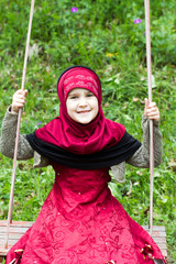 Little muslim girl in a grass
