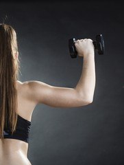 Girl training shoulder muscles lifting dumbbells back view