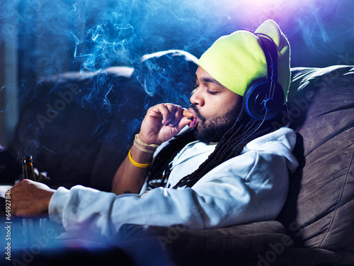 smoking marijuana and drinking beer amid clouds of smoke - 64927840