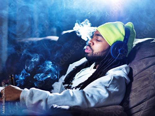 smoking marijuana and drinking beer amid clouds of smoke - 64927877