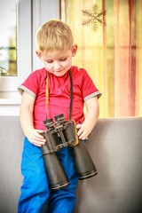 happy boy child kid playing with binoculars. At home.