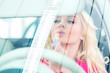 Frau schminkt sich im Auto in Autohaus