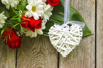Białe wiklinowe serce na drewnianym tle