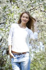 Beautiful girl standing near blooming trees in spring garden