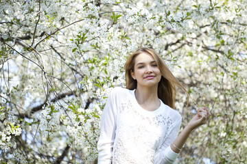 Beautiful young girl standing near blooming trees in spring gard