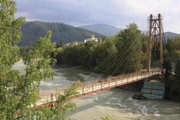 Suspension bridge on the mountain river Katun. Sanatorium Crown