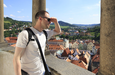 Tourist considers the historical city center from the tower.