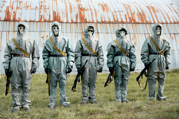 A group of soldiers with guns in their masks and protective clot