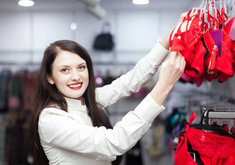female buyer choosing bra at clothing store