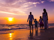 Family walking on the beach - 64933431