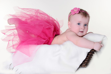Little girl in a basket on a white background