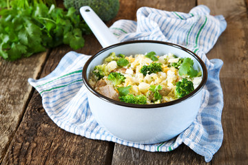 Rice dish with broccoli, meat and eggs on old wooden table