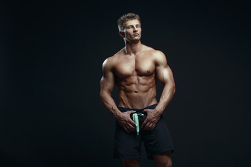 Portrait of a handsome muscular bodybuilder posing over black ba