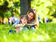 Mother and daughter relaxing in park. - 64935842