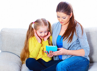 Girl with mother sitting on sofa using tablet