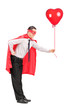 Man in superhero costume holding a red balloon