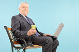 Mature businessman holding a cup and laptop