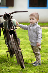 2 years old curious Baby boy walking around the old bike