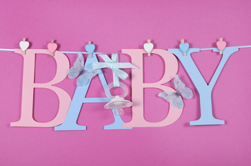 Baby pink and blue letters hanging from pegs a line