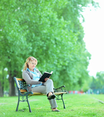 Mature woman reading a book in park