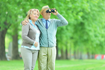 Senior couple looking through binoculars in park