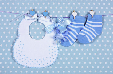 Baby boy socks and bib hanging from pegs on a line