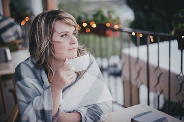 Girl sitting in a cafe wrappet in blanket and drinking coffee