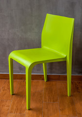 Green chair on the wooden floor with the grey concrete wall