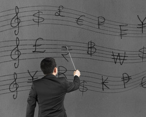 Businessman conducting with money symbols stave on wall