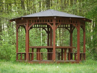 Small brown wooden arbour at edge of forrest