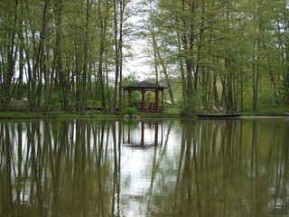 Small wooden arbour at fish pond with pier and chairs