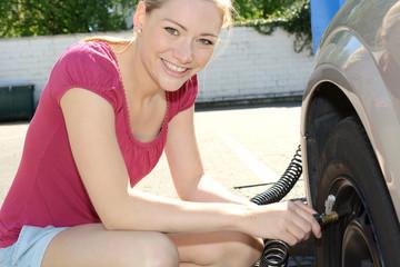 Frau misst Luftdruck in Auto-Reifen