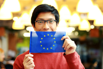 Cheerful asian boy in glasses holding flag of europe union