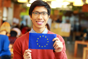 Happy young asian student holding flag of europe union
