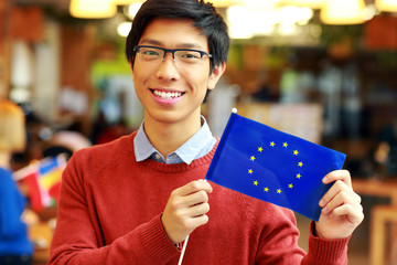 Smiling asian boy in glasses holding flag of europe union