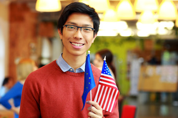 Happy asian boy in glasses holding flag of europe union and USA