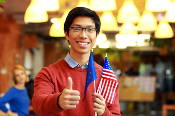 Happy asian boy in glasses holding flag of europe union