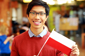 Smiling asian boy in glasses holding flag of Poland