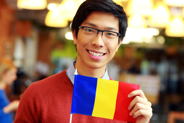 Cheerful young asian boy holding flag of Romania