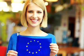 Happy blonde girl holding flag of europe union